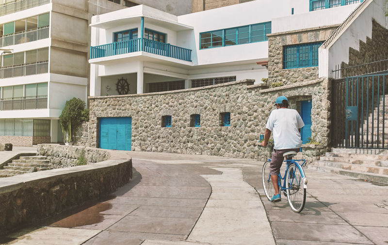 Rear view of man riding bicycle against building in city