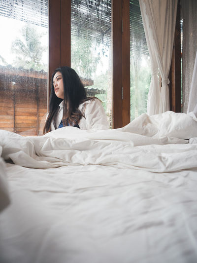 Young woman relaxing on bed at home