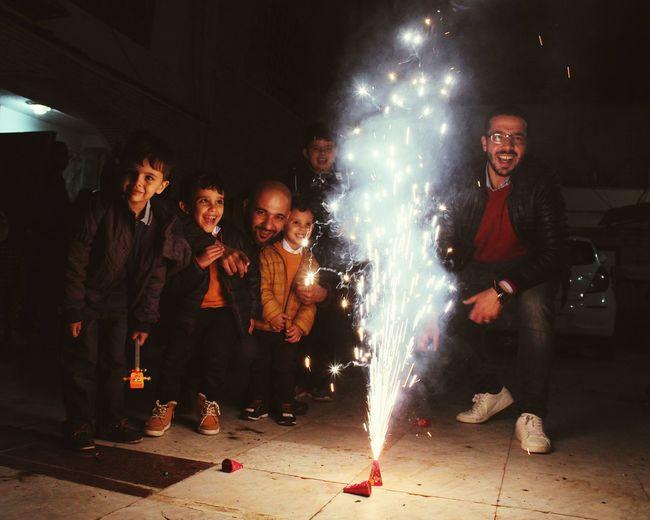 People enjoying firework display on walkway at night