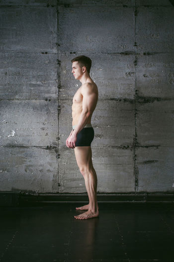 Side view of shirtless muscular man standing by wall