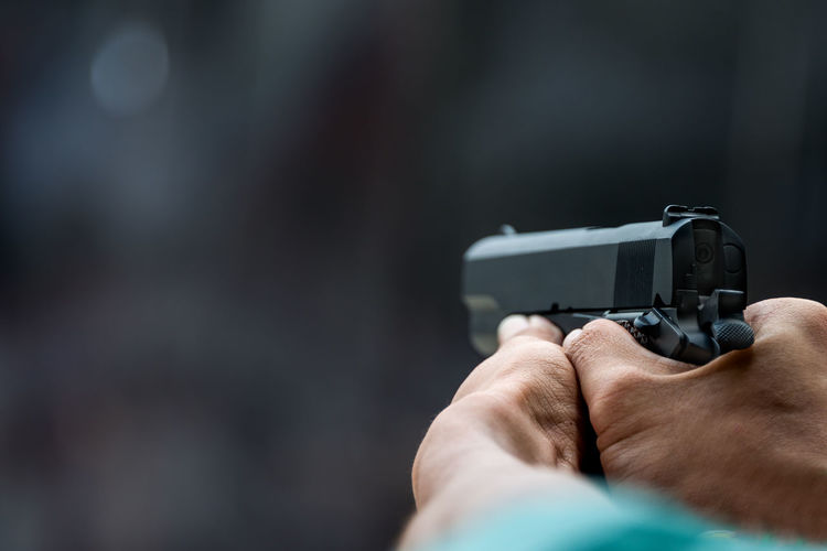 Cropped hands aiming gun