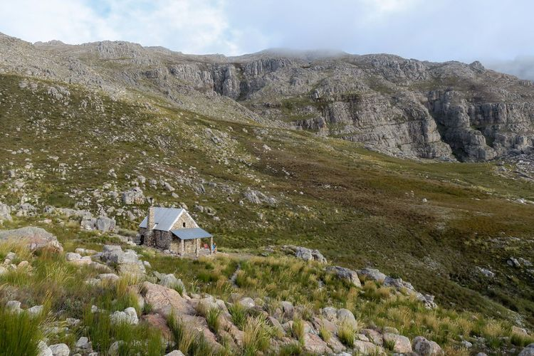 Secluded stone hut in scenic grass covered mountain range Adventure Beauty In Nature Cabin Exploration Explore Grass Grass Hike Hiker Hiking Hills House Hut Landscape Mountain Mountain Range Nature Outdoor Photography Outdoors Rock - Object Scenics Summer Travel View Wilderness