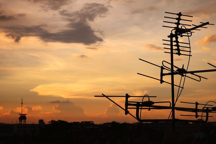 Silhouette of television aerial against sky during sunset