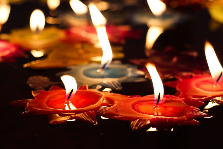 Red Candle with Roses in temple Birthday Candles Burning Candle Celebration Close-up Diwali Diya - Oil Lamp Fire - Natural Phenomenon Flame Focus On Foreground Glowing Heat - Temperature Illuminated Indoors  Lighting Equipment Lit Melting No People Oil Lamp Tea Light