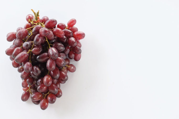 Directly above shot of red berries against white background