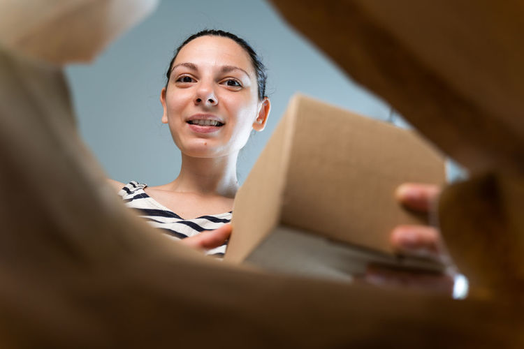 Portrait of beautiful young woman holding mobile phone in box