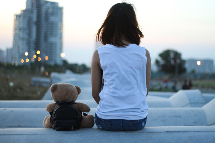 Rear view of woman with teddy bear sitting in city