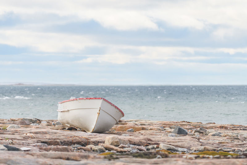 Small boat on rocks Beach Beauty In Nature Boat Cloud - Sky Day Horizon Over Water Nature No People Outdoors Rock - Object Rocks Rocks And Water Scenics Sea Shoreline Sky Stranded Stranded Boat Tranquility Water