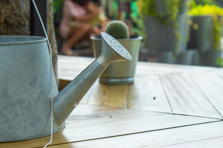 Close-up of watering can on table