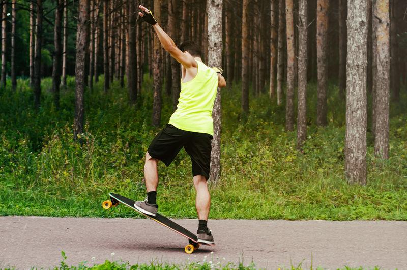 Full length of man skateboarding against trees