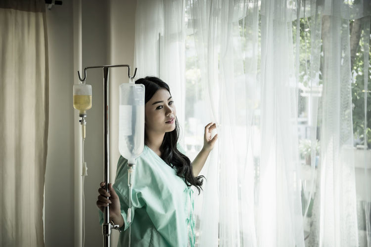 Young woman looking through window while standing by iv drip at hospital