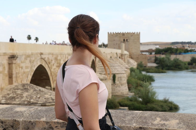 Woman looking at a scenic view of a bridge Built Structure Architecture Water Building Exterior Lifestyles One Person Leisure Activity Rear View Real People Focus On Foreground Sky Young Adult Nature Hairstyle Adult Women Standing Hair Arch Outdoors Bridge - Man Made Structure Looking At View
