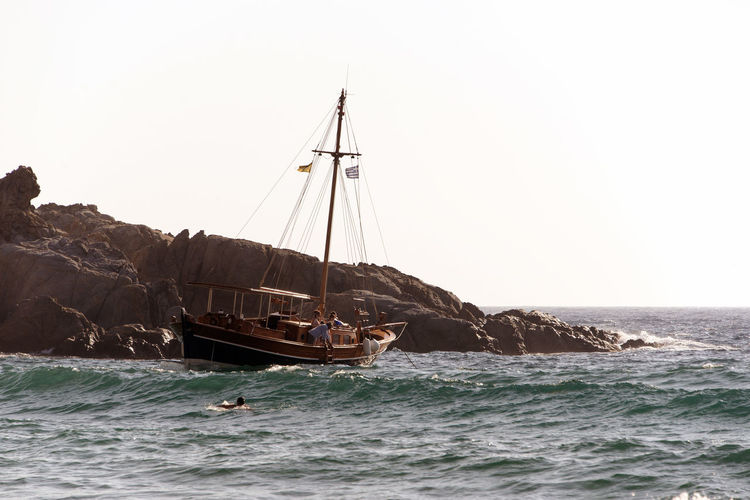 A boat in the waves in the island of Patmos, Greece Greek Islands Wave Beauty In Nature Clear Sky Day Horizon Horizon Over Water Marine Mode Of Transportation Nature Nautical Vessel Outdoors Sailboat Sailing Scenics - Nature Sea Sky Sport Transportation Water Waterfront Women