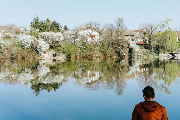 Spring One Person One Man Only Men People Real People Tree Trees Architecture Water Tree Clear Sky Rear View Reflection Lake Sky Countryside Shore Residential Structure Building Greenery Green Country House Lakeside Tranquility Scenics Symmetry Mid Distance Horizon Over Water Waterfront