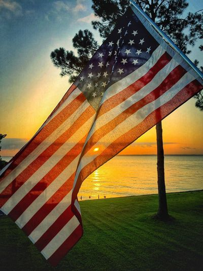 American flag by sea against orange sky