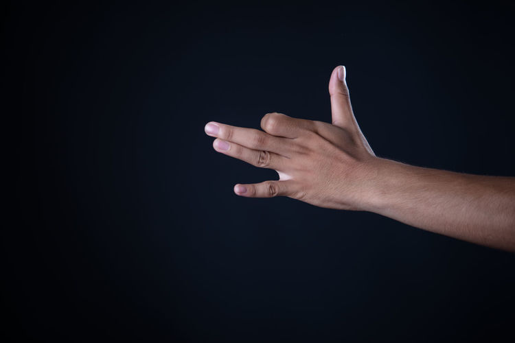 Midsection of person hand against black background