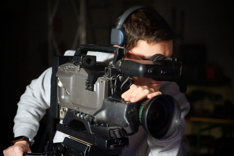 Man filming with video camera at film studio