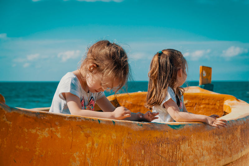 Summer Child Girl Kid Sea Beach Water Sky Boat Fisherman Boat Twins Sisters Sister Real People Leisure Activity Lifestyles Women Togetherness Girls Bonding Childhood Men Boys Nature Males  Females Horizon Over Water Outdoors