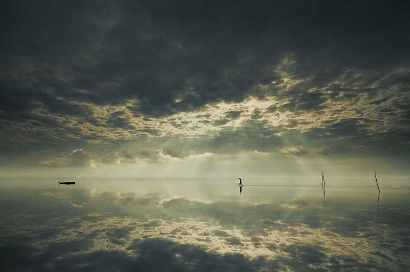 Silhouette man walking at beach against cloudy sky