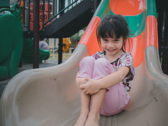 little asian girl smile on playground Childhood One Person Looking At Camera Child Smiling Real People Portrait Happiness Girls Front View Casual Clothing Sitting Females Cute Lifestyles Leisure Activity Emotion Innocence Outdoor Play Equipment Outdoors Hairstyle