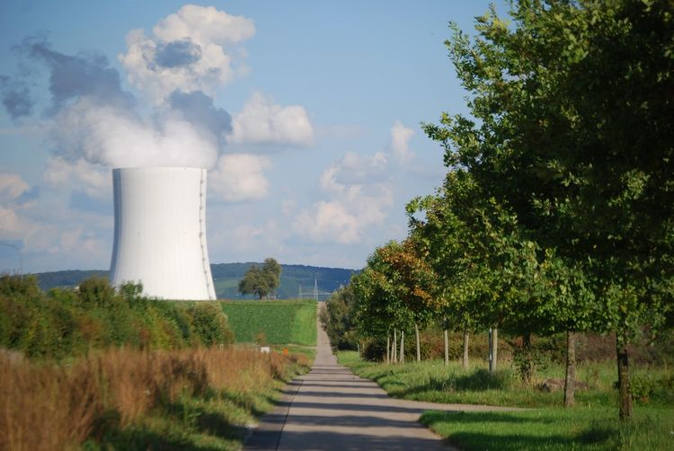 Cooling tower emitting smoke by country road against sky