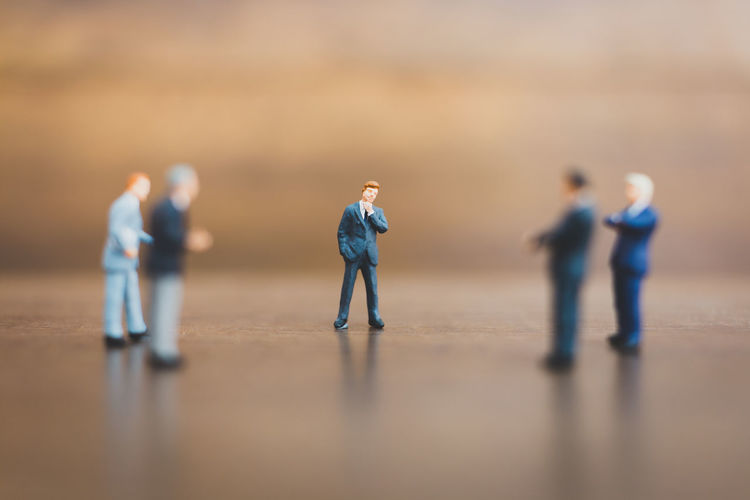 Miniature people businessman standing on wooden background Action Background Business Businessman Closeup Dealer Entrepreneur Figure Leader Little Male Man Men Merchant Mini Miniature Operatorl People person Rich Small Space Suit Tiny Toy Trader Tradesman Tycoon Work