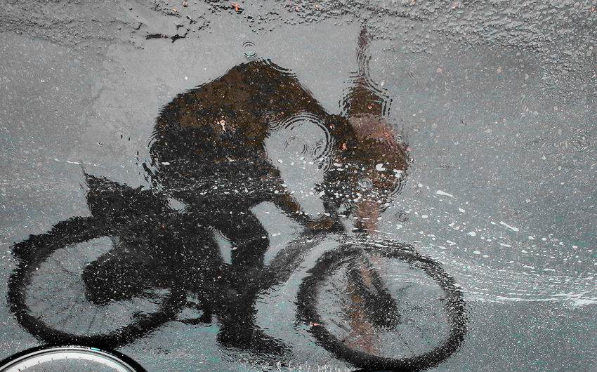 Reflection of person on puddle in street