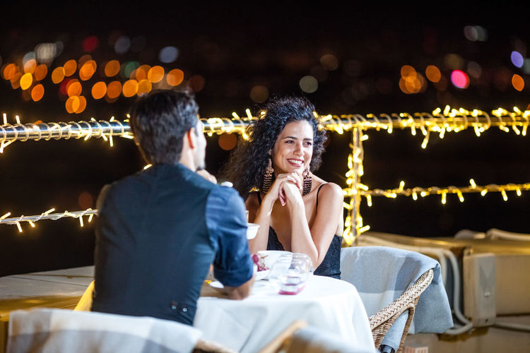 Young Couple Sitting At Table On Illuminated Terrace