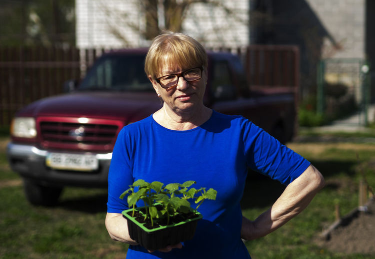 Senior caucasian woman is holds a container with cucumber seedlings. Seedlings Senior Women Caucasian Holds Container Cucumber Glasses Front View Eyeglasses  One Person Real People Focus On Foreground Waist Up Lifestyles Day Casual Clothing Plant Looking At Camera Young Adult Portrait Nature Adult Standing Mature Adult