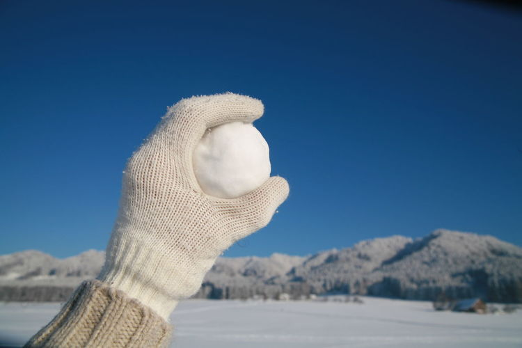 Cropped Hand Holding Snowball Against Clear Blue Sky