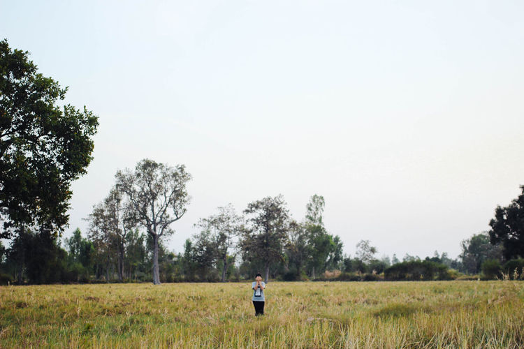 young woman playing hide and seek closed her eyes and face Adult Agriculture Beauty In Nature Casual Clothing Clear Sky Day Field Full Length Grass Growth Landscape Nature One Person Outdoors People Real People Rear View Rural Scene Sky Standing Tranquility Tree Women