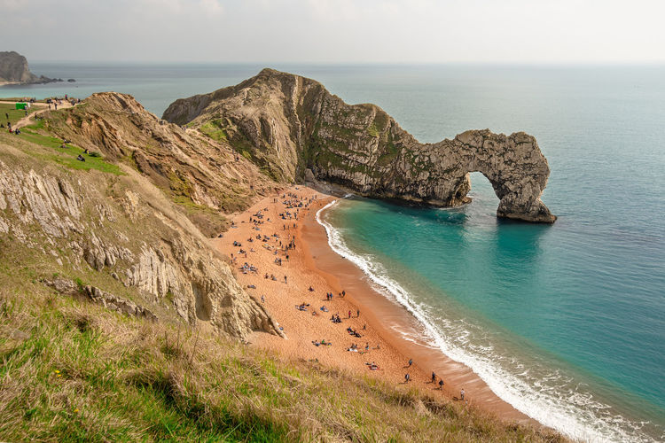 A high up view of the famous limestone arch Durdle Door and golden sand beach from the South West Coastal Path running on top of the near by cliffs, Lulworth Estate, Dorset, England. Beach Blue Sea British Seaside Coast Dorset Durdle Door South Coast. South England Staycation Arch Bay Cliff Face Cliffs Coastal Path Coastline Cove Famous Attraction Jurassic Coast Jurassic Coast Footpath Natural Arch Public Footpath Rock Formation Rock Pinnacle Tourism Tourist Attraction  Water Sea Beauty In Nature Land Horizon Horizon Over Water Scenics - Nature Sky Tranquility Tranquil Scene Rock Nature Rock - Object Solid Day Idyllic Non-urban Scene No People Outdoors