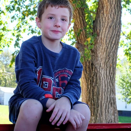 Portrait of boy sitting on bench in park