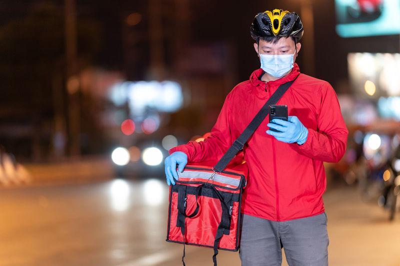 Portrait of man holding red umbrella standing on street