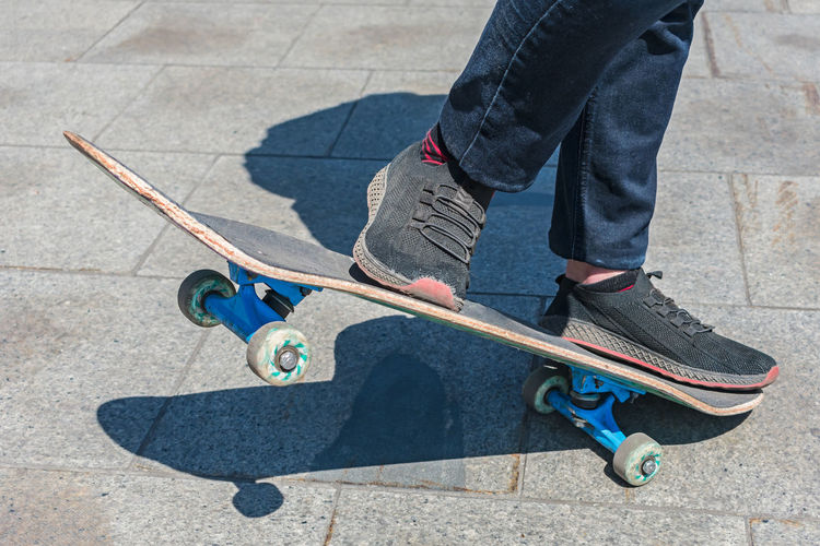 Low section of man skateboarding on street