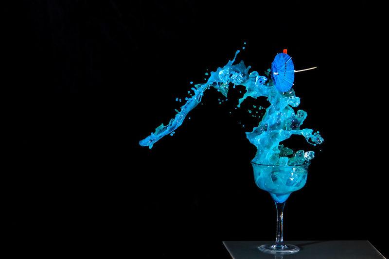 Close-up of blue drink splashing against black background