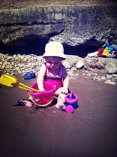 mi pequeñita preciosa su primera experiencia en la arena.. un poko mas y se come un pastel de arena!!