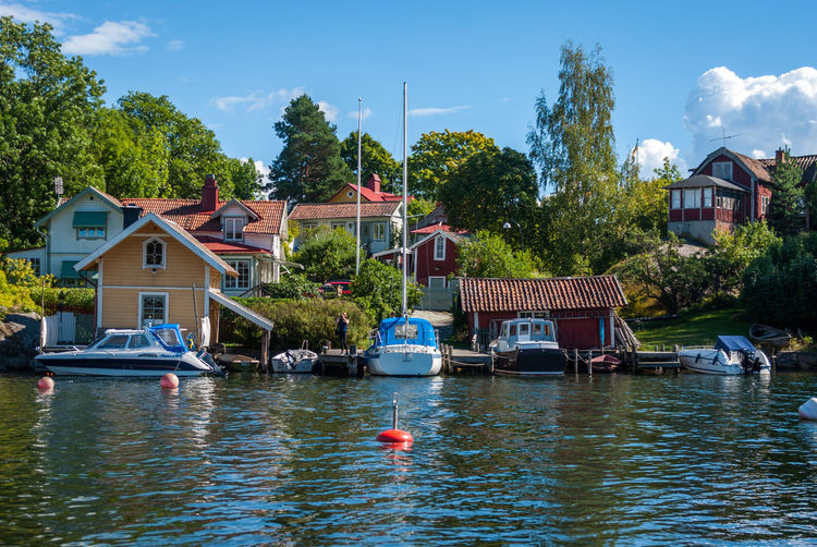 Boats moored on lake by houses