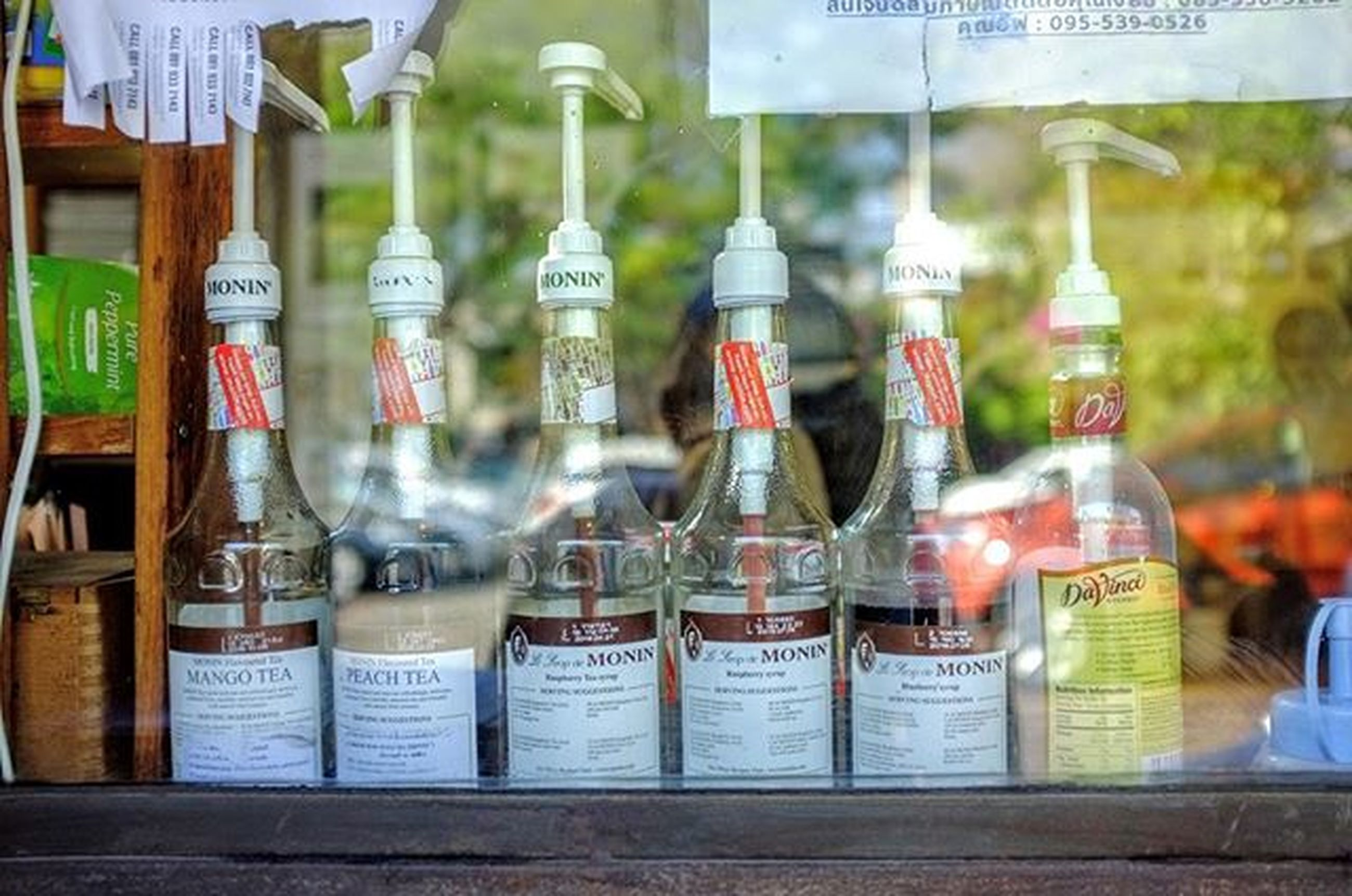 indoors, text, for sale, glass - material, western script, variation, retail, food and drink, choice, arrangement, store, still life, non-western script, large group of objects, close-up, shelf, communication, focus on foreground, transparent, bottle