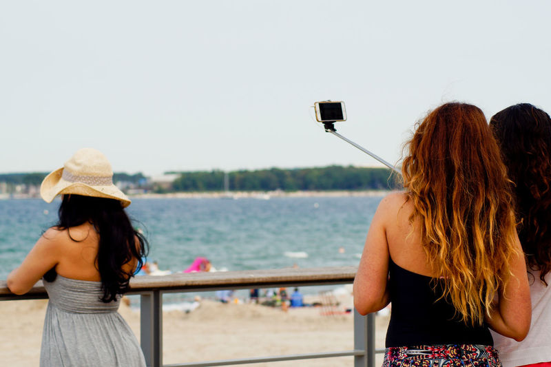 Rear view of friends taking selfie while standing by railing against sea
