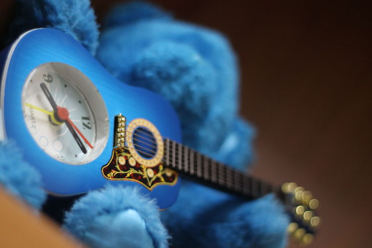 Low angle view of toy guitar clock and teddy bear against black background