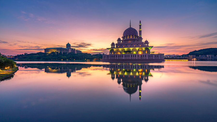 Reflection of mosque in lake against sky during sunset