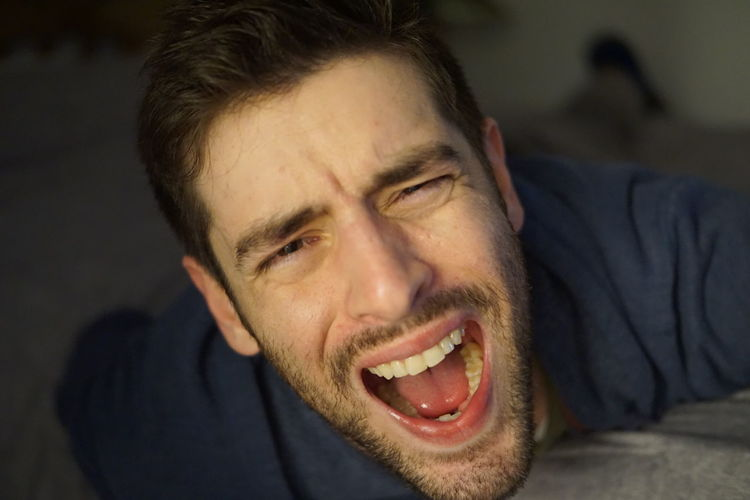 Close-up portrait of man screaming outdoors
