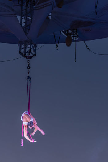 Low angle view of woman hanging on rope