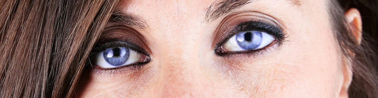 Cropped portrait of woman wearing purple contacts lens