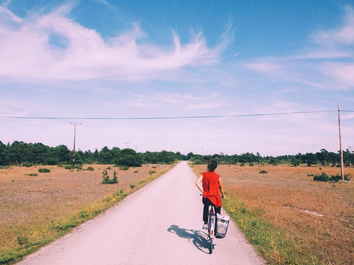 Rear view of woman riding bicycle on single lane road against sky