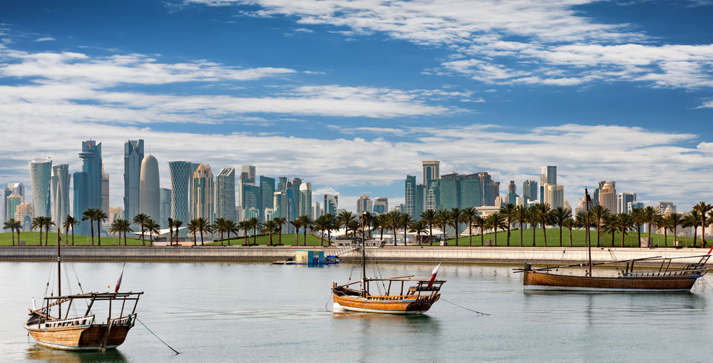 The skyline of Doha, Qatar, on a sunny day Arabian Doha Modern Sunny Architecture Bay Blue Boats Building Exterior Built Structure City Cityscape Clear Cloud - Sky Day Islam Nautical Vessel No People Outdoors Park Qatar Sky Skyscraper Water Waterfront