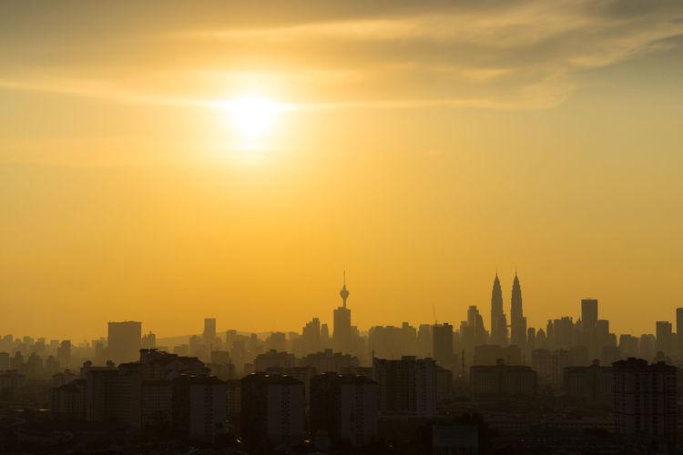 Buildings in city against orange sky during sunset