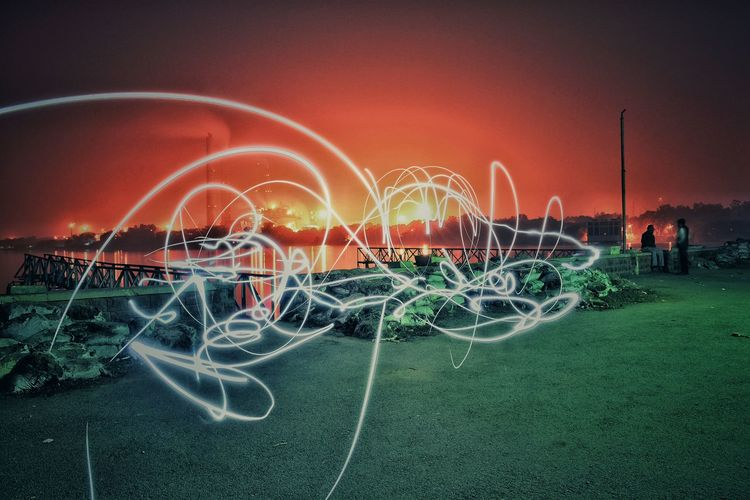 Light Painting Over Grassy Field Against Orange Sky During Sunset