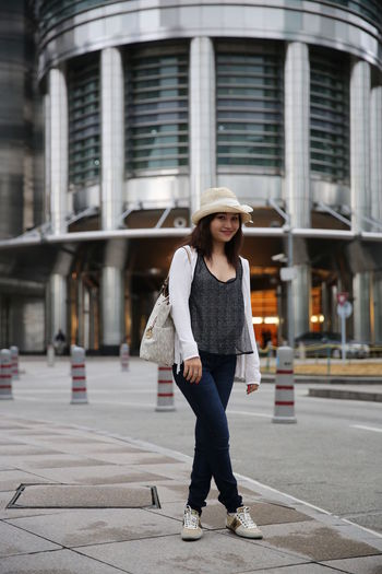 Portrait of young woman standing on sidewalk against modern building in city